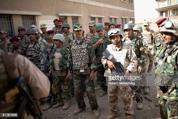 Iraqi Army soldiers line up before crossing the concrete barrier dividing Sadr City to take control of the 25 million Shia dominated stronghold of...