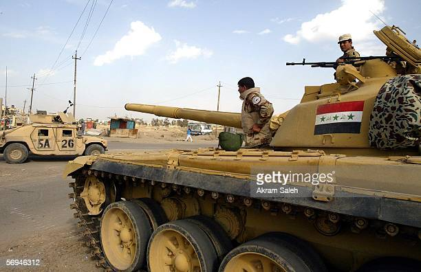 Iraqi army soldiers man a checkpoint as a U.S army vehicle passes by February 27, 2006 northwest of Baghdad, Iraq. Four people were killed and 17...