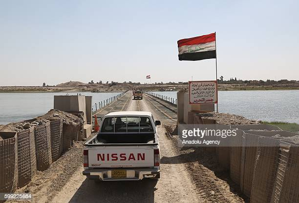 Iraqi Army soldiers passes from a temporary bridge over Tigris River as they petrol at Qayyarah Town recently freed from Daesh terrorists in Mosul...