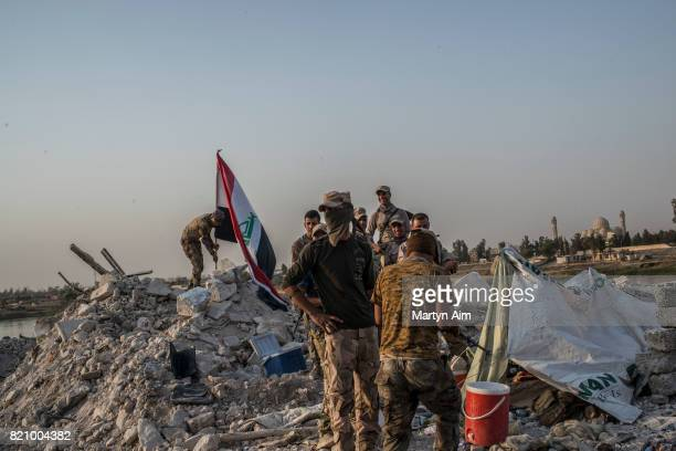 Iraqi Army soldiers place an Iraqi flag beside the Tigris River in the destroyed Old City district on July 22 2017 in Mosul Iraq Despite the declared...