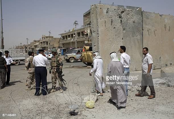 Iraqi Army soldiers speak with National Policemen as civilians cross the concrete barrier dividing Sadr City the 25 million Shia dominated stronghold...