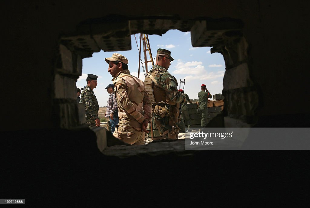 Iraqi Army troops stand in a field headquarters behind the frontline with ISIL on April 14, 2015 near Al-Karmah, in Anbar Province, Iraq. Iraqi government forces are assaulting ISIL fighters on frontline positions which were established last year when ISIL captured much of the province.