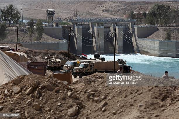 Iraqi army vehicles are stationned in front of a dam on the Euphrates River on April 14 2015 in the Garma district west of the Iraqi capital Baghdad...