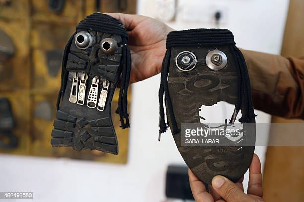 Iraqi artist Akeel Khreef shows some of his art pieces depicting jihadists on the soles of wornout shoes on January 13 2015 in Baghdad Akeel Khreef...