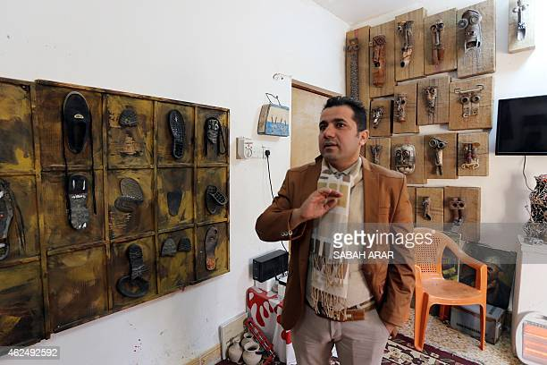 Iraqi artist Akeel Khreef stands in front of his art pieces depicting jihadists made on wornout shoes on January 13 2015 at his workshop in Baghdad...