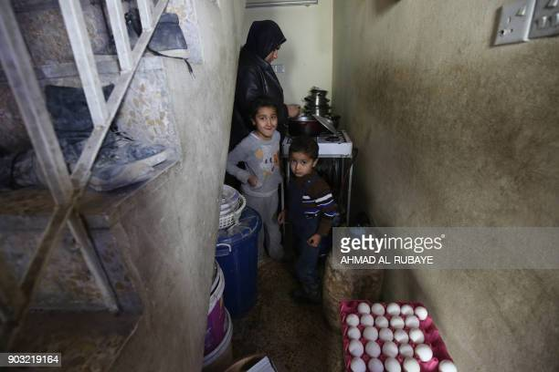 Iraqi Asma Mohammed whose husband and parents were killed in the battle of Mosul stands with her children at their home in Mosul's Old City on...