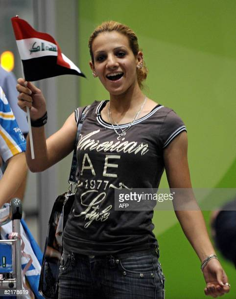 Iraqi athlete Dana Hussein smiles and waves her countries national flag as she arrives at Beijing international airport in Beijing on August 4 2008...