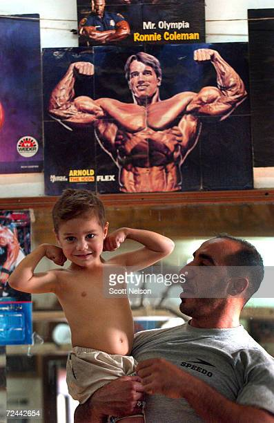 Iraqi bodybuilder Kathem holds four-year-old Abdullah Talib as he mimics the poster of former bodybuilder turned actor Arnold Schwarzenegger at the...