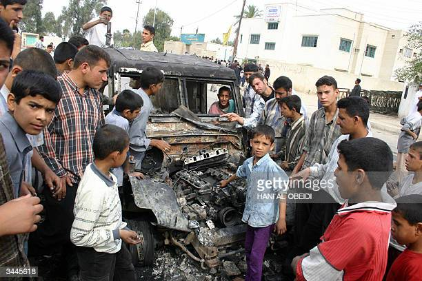 Iraqi boys gather arounded a wrecked British army armored vehicle in the southern city of Amara 19 April 2004 Clashes between supporters of Iraqi...