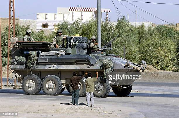 Iraqi boys give the thumbs up to US Marines patrolling on September 14 2004 in the Iraqi Holy city of Najaf Weeks of battles between the US military...