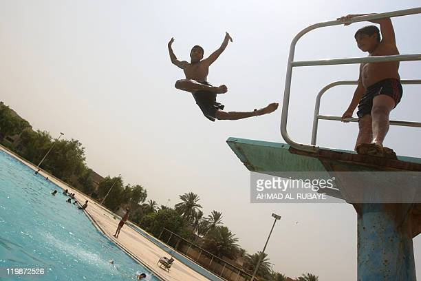 Iraqi boys jump off a diving board into a public swimming pool in central Baghdad as temperatures sore to 50 degrees Celsius on July 11 2011 AFP...