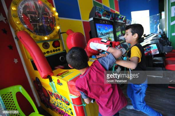 Iraqi boys play a boxing game in an arcade as families visit the vast Baghdad Island amusement park on the northern outskirts of the capital which...