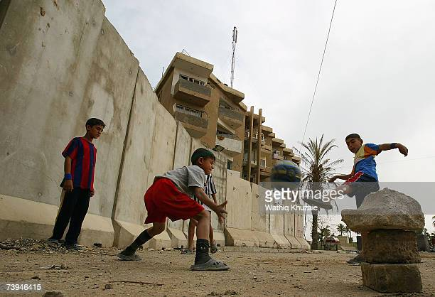 Iraqi boys play football near a blast wall on April 22 2007 in the Karrada neighborhood of Baghdad Iraq US troops are building a wall that the...
