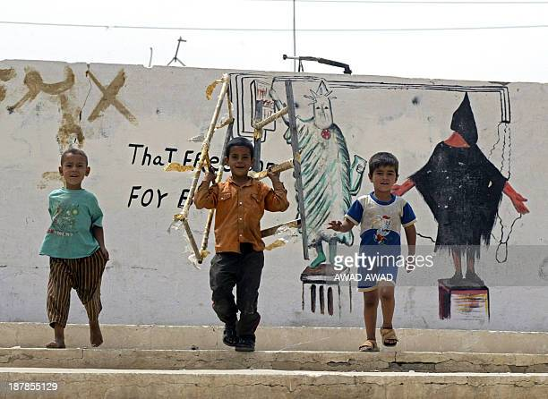 Iraqi boys play in front of a mural depicting the Statue of Liberty and a painting copied from a widely published photograph taken in the USrun Abu...