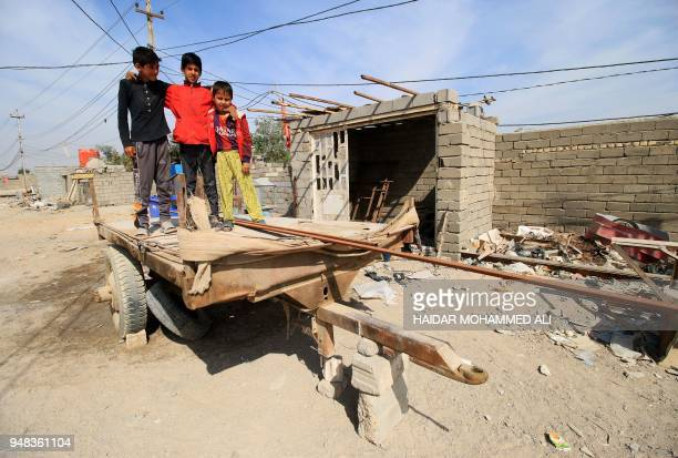 Iraqi boys pose for a photo on a trailer in alZubair south of Basra on February 11 2018 Informal housing settlements are flourishing in the oilrich...