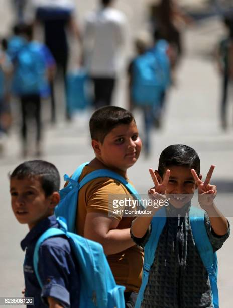 Iraqi boys walk to school in west Mosul on July 27 2017 As the Iraqi government has said it does not recognise schooling under IS which seized...