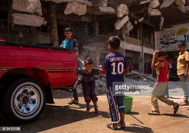 TOPSHOT Iraqi boys wash a vehicle in west Mosul on July 12 2017 a few days after the government's announcement of the 'liberation' of the embattled...