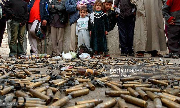 Iraqi bystanders stand among spent shell casings where US soldiers allegedly conducted a raid in which one Iraqi was killed in the Sadr city...