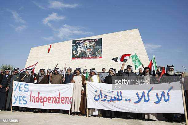 Iraqi chiefs of tribes and clans hold a banner that reads in Arabic 'No No to the Enemy' as they protest against the controversial security pact with...