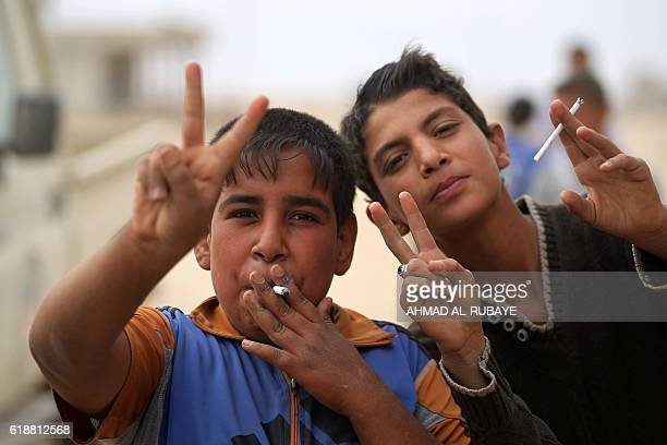 Iraqi childen smoke cigarettes upon the arrival of Iraqi forces in the village of Umm Mahahir south of Mosul on October 28 2016 after troops...
