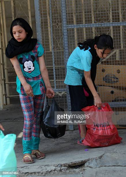 Iraqi children carry bags on August 31 2016 during a food distribution for displaced and impoverished families at the shrine of the Sunni Sheikh...