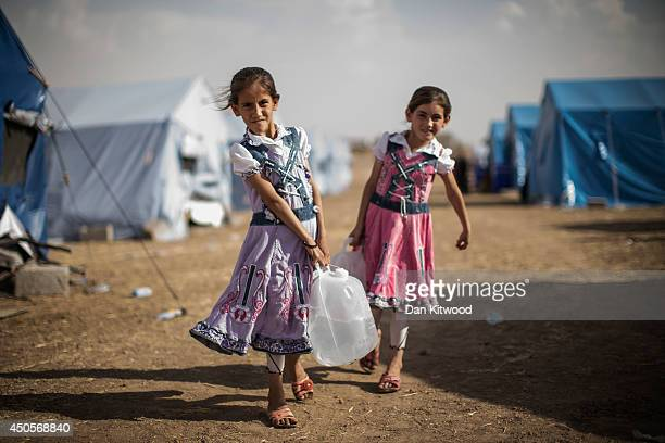 Iraqi children carry water to their tent at a temporary displacement camp set up next to a Kurdish checkpoint on June 13, 2014 in Kalak, Iraq....