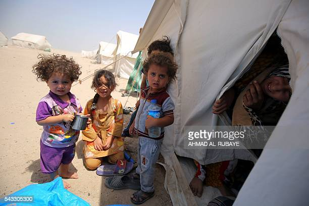 Iraqi children displaced from the city of Fallujah gather next to a tent at a newly opened camp where hundreds of displaced Iraqis are taking shelter...