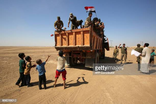Iraqi children from a neighbouring village wait to receive food supplies distributed by Iraqi forces and fighters from the Hashed alShaabi as the...