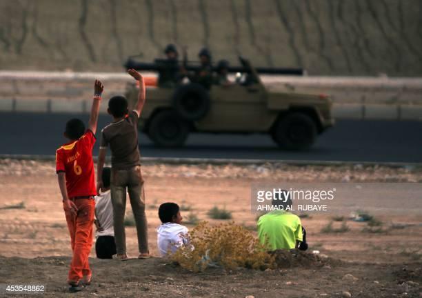 Iraqi children from the Yazidi community wave to Kurdish Peshmerga forces near Dohuk the Kurdish region of autonomous Kurdistan in Iraq after they...