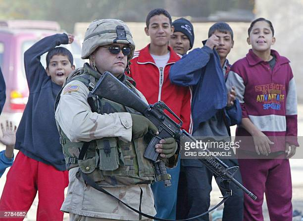 Iraqi children gather around a US soldier as he scans the area where a US military convoy came under attack 05 December 2003 in Baghadad Two bomb...