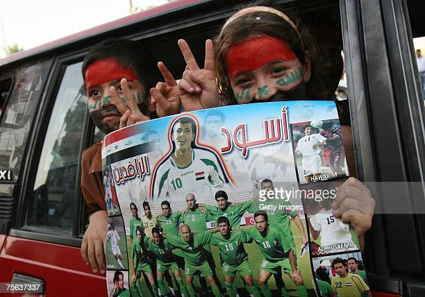 Iraqi children hold a poster of the Iraq National soccer team after their team won against South Korea during the 2007 AFC Asian Cup semifinal soccer...