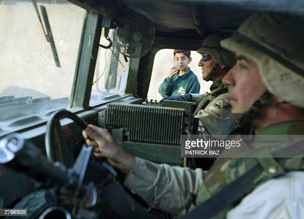 Iraqi children look into a US military vehicle passing through Baghdad's Azamiyah neighborhood 28 November 2003 Former US first lady Senator Hillary...