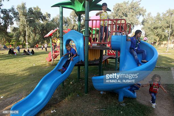 Iraqi children play at an amusement park during the Muslim holiday of Eid alAdha in the capital Baghdad on October 6 2014 The religious festival...