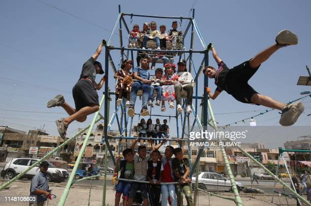 TOPSHOT Iraqi children play in a amusement park in Baghdad's eastern suburb of Sadr City during Eid alFitr on June 05 2019 Muslims worldwide...
