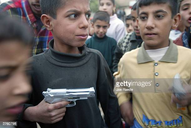 Iraqi children play with a toy gun as they celebrate Eid alFitr November 25 2003 in Baghdad Iraq The Shiite muslims celebrated the Eid alFitr a day...