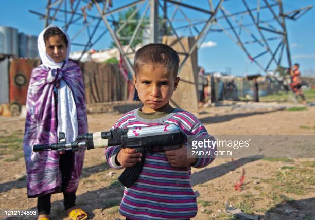 Iraqi children play with a toy gun in the northern city of Mosul on May 8, 2020 during the Muslim holy fasting month of Ramadan as Iraq eases...