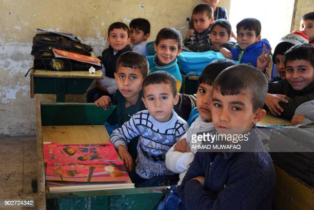 Iraqi children pose for a photo in a classroom in the battered city of Mosul on December 27 2017 Through games mime and sport an instructor aims to...