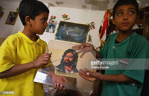 Iraqi children show a picture of Imam Ali following a predawn raid on May 6 2007 in the Sadr city Shiite neighborhood of Baghdad Iraq Several houses...
