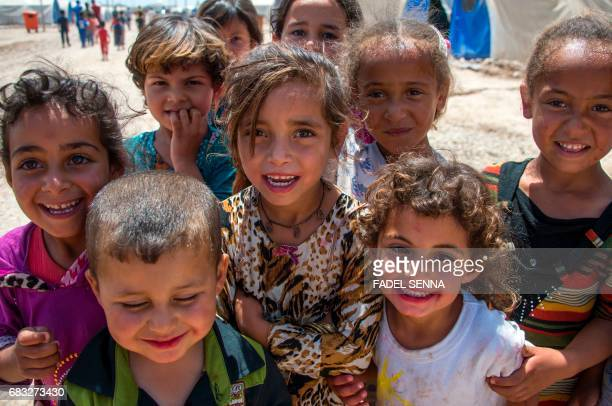 Iraqi children stand at a camp for internally displaced people in Hammam alAlil on May 14 after fleeing west Mosul due to the government forces...