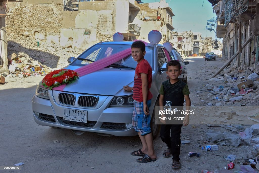Iraqi Children Stand Next To A Car That Has Been Decorated For The First Wedding In Old City Of Mosul Year After Was Retaken By