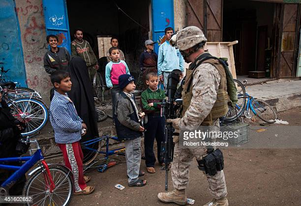 Iraqi children stare at a US Marine patrolling February 17 2007 in the Husayba Iraq downtown market area Husayba a strategic border crossing with...