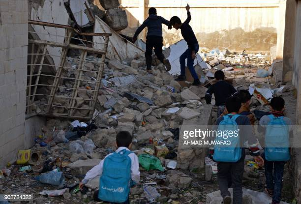 Iraqi children walk in the rubble as they head to school in the battered city of Mosul on December 27 2017 Through games mime and sport an instructor...