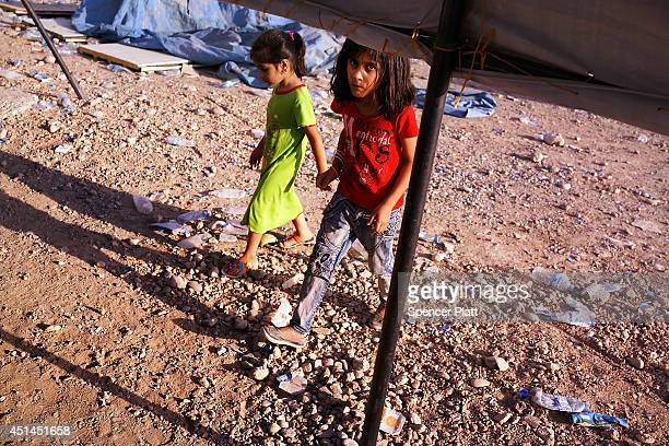 Iraqi children walk through a displacement camp for those caughtup in the fighting in and around the city of Mosul on June 28 2014 in Khazair Iraq...