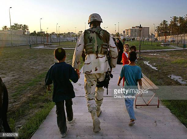 Iraqi children walk with a member of the 1st 153rd Infantry Arkansas Army National Guard at a new playground July 2 2004 in Baghdad Iraq The...