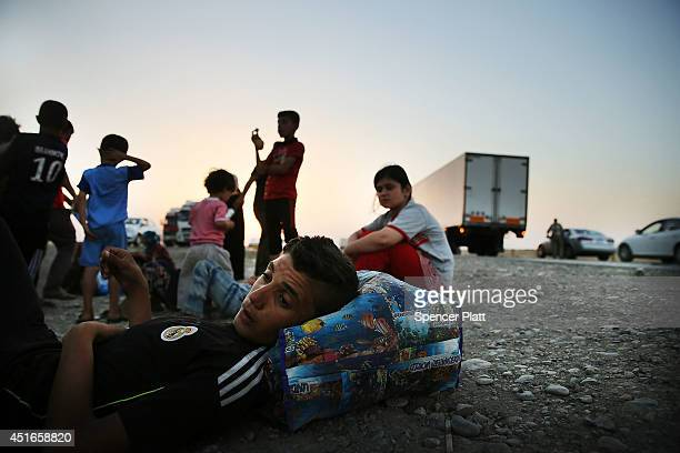 Iraqi children who fled recent fighting near the city of Mosul prepare to sleep on the ground with their familyas they try to enter a temporary...