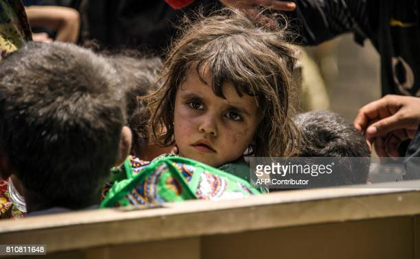 Iraqi children who fled the fighting between government forces and Islamic State group jihadists in the Old City of Mosul sit in a vehicle in the...