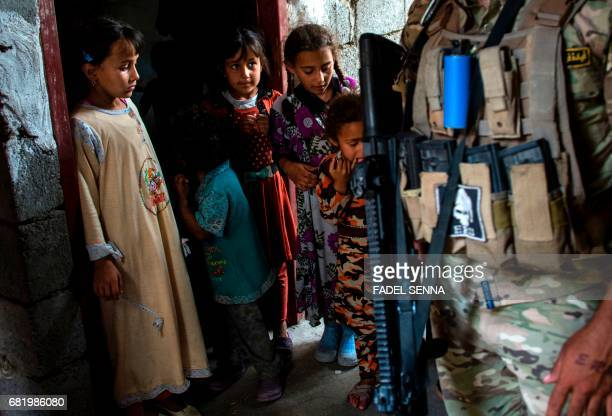 TOPSHOT Iraqi children who spent one week confined to their house because they were scared to leave due to the fighting stand in the doorway of their...