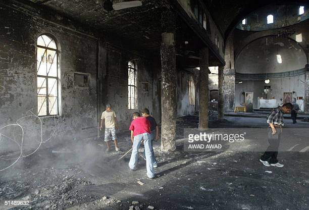Iraqi Christian boys sweep th floor at the badly damaged St George Catholic Church 17 October 2004 in the Karrada neighborhood of Baghdad prior to...