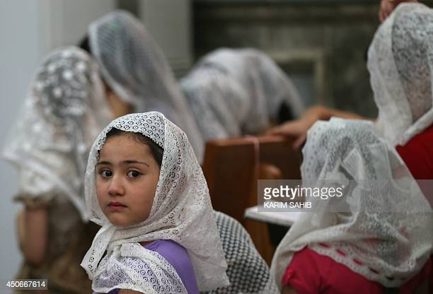 Iraqi Christian children gather inside the Church of the Virgin Mary for prayers in the town of Bartala on June 15 east of the northern city of Mosul...