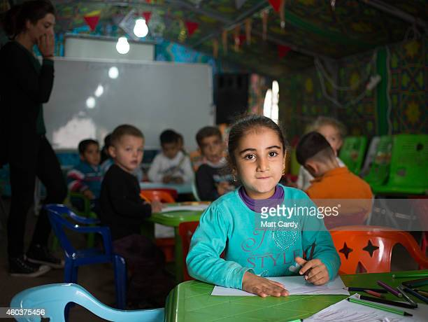 Iraqi Christian children have school lessons in a tent erected in the grounds of Mazar Mar Eillia Catholic Church in Ankawa that has now become home...